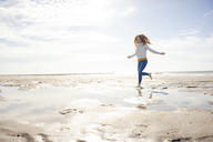 Netherlands, Zeeland, happy redheaded woman relaxing on the beach - KNSF04198
