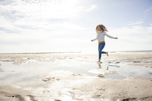 Netherlands, Zeeland, happy redheaded woman relaxing on the beach - KNSF04198