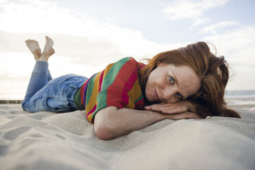 Netherlands, Zeeland, portrait of smiling woman lying in the sand on the beach - KNSF04204
