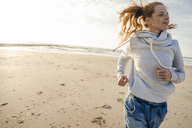 Netherlands, Zeeland, redheaded woman jogging on the beach - KNSF04207