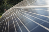A man inspecting the surface of a large tilted solar panel installation for harnessing the energy of the sun. - MINF00469