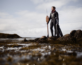 A man in a wetsuit, standing on the shore with a large spear fishing harpoon. - MINF00475
