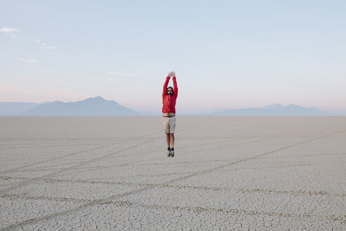 A man jumping in the air on the flat desert or playa or Black Rock Desert, Nevada. - MINF00502