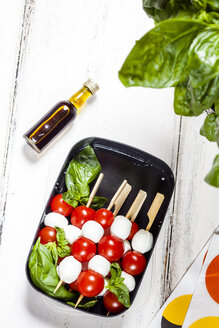 Lunch box of skewered cherry tomatoes and mozzarella cheese balls with basil leaves - SBDF03669