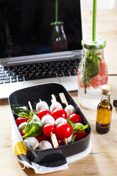 Lunch box of Caprese salad, bottle of infused water and laptop on desk - SBDF03672