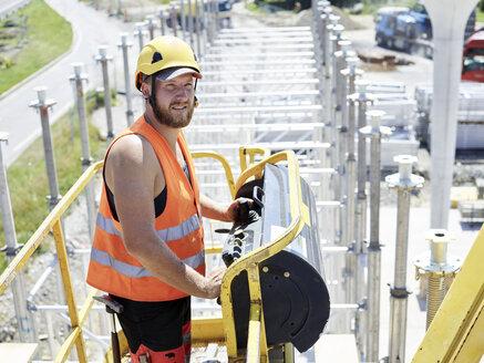 Worker on construction site navigating hoist - CVF00977
