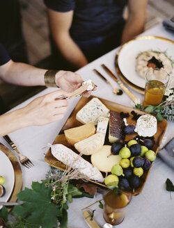 A table laid with a white cloth and place settings seen from above. An organic cheese board with soft and hard cheeses and figs. Two people sitting at the table. - MINF00567
