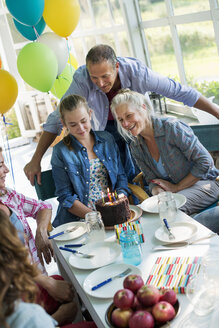 A birthday party in a farmhouse kitchen. A group of adults and children gathered around a chocolate cake. - MINF00603