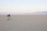 Man with camera and tripod on the flat saltpan or playa of Black Rock desert, Nevada. - MINF00722