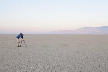 Man with camera and tripod on the flat saltpan or playa of Black Rock desert, Nevada. - MINF00722