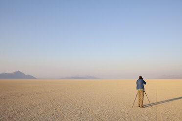 Man with camera and tripod on the flat saltpan or playa of Black Rock desert, Nevada. - MINF00728