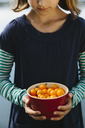 Nine year old girl holding bowl of organic yellow cherry tomatoes - MINF00740