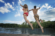 Two young people, boy and girl, running and leaping off the jetty into a lake or river. - MINF00764