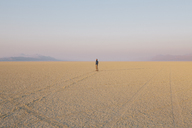 The figure of a man in the empty desert landscape of Black Rock desert, Nevada. - MINF00794