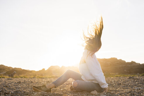Young woman at the beach, tossing hair at sunset - AFVF00885