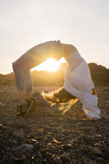 Young woman at the beach, doing wheel pose at sunset - AFVF00888