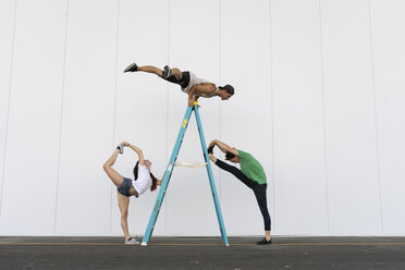 Three acrobats doing tricks on a ladder - AFVF00899