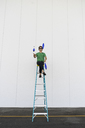 Acrobat wearing sunglasses, sitting on ladder, juggling - AFVF00908