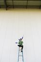 Acrobat wearing sunglasses, sitting on ladder, juggling - AFVF00911