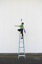 Acrobat standing on ladder, juggling - AFVF00914