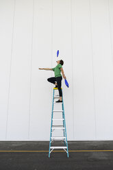 Acrobat standing on ladder, juggling - AFVF00914