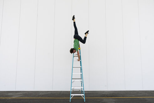 Acrobat balancing upside down on a ladder - AFVF00917