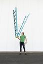 Acrobat balancing ladder upside down in his hand - AFVF00935
