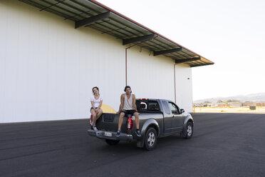 Two acrobats sitting on car bonnet, taking a break - AFVF00938