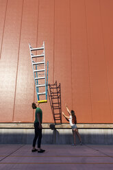 Acrobat balncing ladder on his face while colleague is trying to catch its shadow - AFVF00947