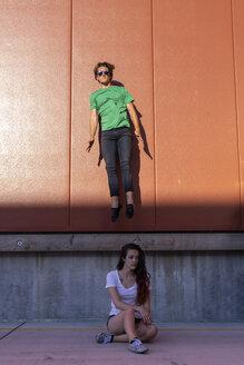 Acrobat jumping mid-air behind sitting woman, looking sad - AFVF00950