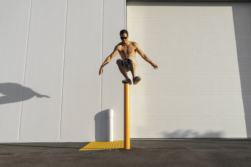 Acrobat jumping from pole, wearing sunglasses - AFVF00971