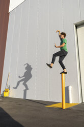 Acrobat standing on pole, casting shadow at cleaning bucket - AFVF00974