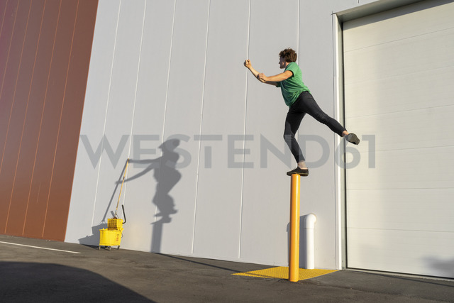 Acrobat standing on pole, casting shadow at cleaning bucket - AFVF00977