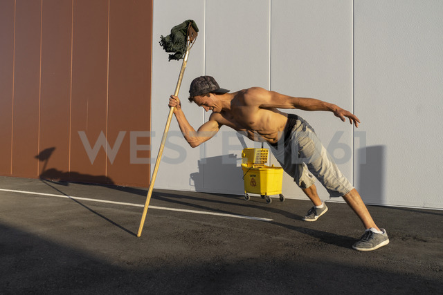 Acrobat playing with cleaning bucket and mop - AFVF00983