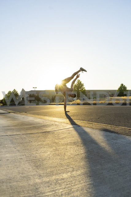 Acrobat practicing one-armed handstand on a road at sunset - AFVF00992