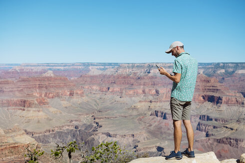USA, Arizona, Grand Canyon National Park, Grand Canyon, man looking at smartphone - GEMF02167