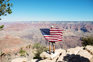 USA, Arizona, back view of man with American flag enjoying view of Grand Canyon National Park - GEMF02170