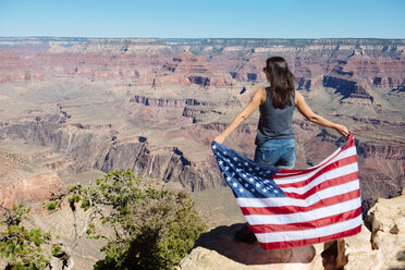 USA, Arizona, back view of woman with American flag enjoying view of Grand Canyon National Park - GEMF02173