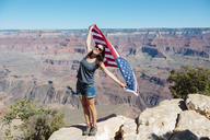 USA, Arizona, smiling woman with American flag at Grand Canyon National Park - GEMF02176