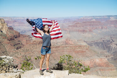 USA, Arizona, smiling woman with American flag at Grand Canyon National Park - GEMF02179