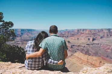 USA, Arizona, Grand Canyon National Park, back view of couple sitting side by side looking at view - GEMF02197