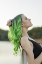 Profile of young woman with dyed green hair and eyebrows in nature - AFVF01011