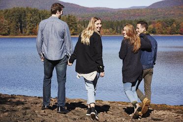 Four people walking along, couples hand in hand, on the shore of a lake. - MINF01037