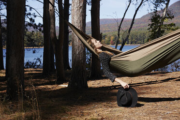 A woman lying in a hammock relaxing, under the pine trees by a lake. - MINF01040