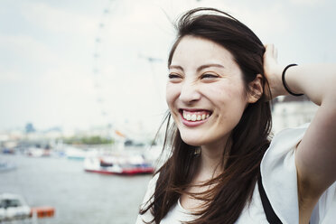 Young Japanese enjoying a day out in London, standing by the River Thames, London Eye in the background. - MINF01085