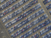 Aerial view of a car distribution centre, new cars parked in rows on a lot ready for sale. - MINF01118