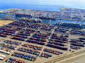 Aerial view of the container port at San Pedro in Los Angeles, with ships docked and containers awaiting loading. A commercial freight dockyard. - MINF01121