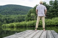 A man standing on a wooden pier overlooking a calm lake. - MINF01241