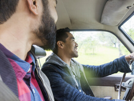 Two young men in a car, driver and passenger, smiling. - MINF01328