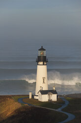 The historic Yaquina Head tower lighthouse on a headland overlooking the Pacific coastline. - MINF01475